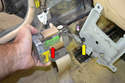 Remove the green wiring harness (red arrow) and clip the zip tie where it mounts to the bracket (yellow arrow).