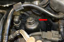 Place your 27mm socket over the filter housing (red arrow) and loosen it.