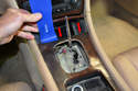 Open the ash tray and use your trim removal tool to gently pry up the front of the shifter plate (red arrows).