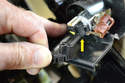 Disconnect the cigarette lighter wiring (yellow arrow).