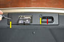 Using a T20 Torx remove the two screws (yellow arrows) holding the trunk release plate.