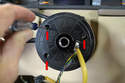 If the wheel was level when you took it off you will see the three small Philips head screws (red arrows) holding wiring ring on.