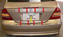 There is a fascia or cover over the rear of the trunk that is held on by eight push clips (red arrows, hidden) and one shear or security bolt (yellow arrow).