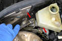 Use a 12mm flared nut wrench and remove the two brake lines (red arrows) from the master cylinder.