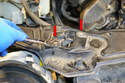 Use a 10mm wrench and remove the two bolts (red arrows) holding down the hood releases on both sides of the cross member.