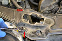 Remove the upper two 10mm bolts (red arrows) on each side of the cross member.