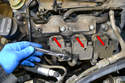 Use a T-30 Torx and remove the three bolts (red arrows) holding the coil packs in place.