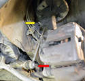 This photo illustrates the drop link that attaches the sway bar (red arrow) to the strut (yellow arrow).