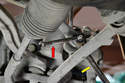You will need to remove the lower link from where it attaches to the stabilizer bar by holding the large nut (yellow arrow) with a 16mm wrench and turning the smaller inner bolt (red arrow) with a 7mm.