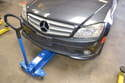 When using a hydraulic floor jack to lift the front of the vehicle, place the hydraulic floor jack under the lift pad at the front section under the vehicle.