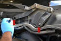 Use a trim removal tool and pry the caps off the two arms for the passenger side (red arrows).