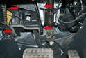 Remove the cover over the brake pedal assembly by gently prying the four clips out and removing the cover (red arrow).