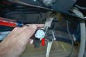 Insert the key into the lock and turn it until the ball end of the latch cable can be removed from the plastic wheel (red arrow).