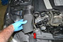 Remove the air duct by compressing the back of the engine cover and then sliding it off the front air duct (red arrow).