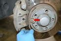 Next, use a large flathead screwdriver and a set of pliers to remove the pad retention spring (red arrow).