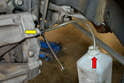 Attach a drain hose to a catch bottle (red arrow), and then open the bleed nipple with the flared nut wrench (yellow arrow).