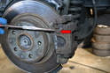 Use a set of pliers and pry the retaining spring out from the front of the caliper (red arrow).