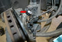 Using a 21mm socket remove the nut on the bolt that connects the top of the steering knuckle to the strut (red arrow) but leave the bolt in place.