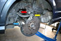 With the dust shield free to move, you can spin it around and remove the camber strut (red arrow), torque strut (yellow arrow), tie rod (blue arrow) and the control arm (not shown) where they connect to the wheel carrier.