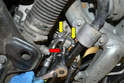 Use a 13mm socket and remove the power steering line (red arrow) from the lower mount on the alternator.