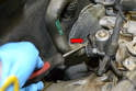 Next use a flathead screwdriver and pry up the quick release clip on the heater hose (red arrow).