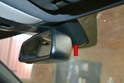 The sensor is located under a plastic protective cover behind the rear view mirror and attached to the windshield (red arrow).