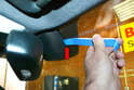 Use a trim removal tool and gently pry the cover off the mount attached to the windshield (red arrow).