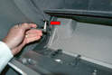 Use a T20 Torx and remove the screw in the bottom corner of the box near the center console (red arrow).