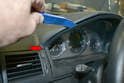 Use your trim removal tool and gently pry the top of the trim piece downwards and out while pulling it out from the sides.