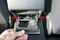 To remove the ashtray, partially open it and slip a trim removal tool between the plastic surround and the rear of the ashtray.