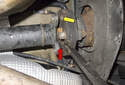 With the driveshaft fasteners removed, use a pry bar to lever the driveshaft (red arrow) out of the flex-disc aligning tab (yellow arrow).