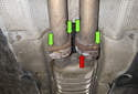 If you're replacing the right side and center mufflers, remove the four 13mm flange fasteners (green arrows).
