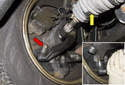 Working at the left side tie rod end, remove the 21mm mounting nut (red arrow).