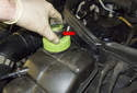 Once the cap is removed, install the pressure tester adapter (red arrow) to the coolant expansion tank.