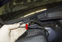Working at the right side of the wiper cowl, remove the washer hose from the mount (red arrow).