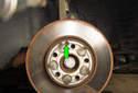 Front Brake Rotor Remove the T40 Torx fastener (green arrow).