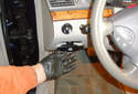 Working inside the vehicle on the driver side, release the parking brake by pulling on the parking brake release handle.