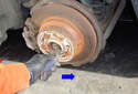 Lever the flathead screwdriver in the direction of the blue arrow to loosen the adjustment so you can remove the brake drum if necessary.