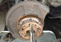 Spin the hub flange until one of the large holes lines up with the parking brake shoe mounting springs.