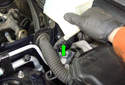 Squeeze the lower hose clamp (green arrow) and remove the lower reservoir hose from the brake fluid reservoir.
