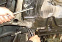 Remove the rear lower control arm fastener using a 21mm deep socket and a 21mm wrench.