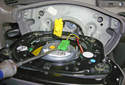Using a flathead screwdriver, lever up on the green connector to remove it from the airbag.