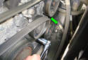 Then remove the accessory drive belt from the tensioner pulley in the direction of the green arrow.