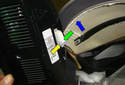 While pushing in on the locking tab (green arrow) slide the locking lever (yellow arrow) in the direction of the blue arrow.