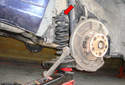 As you jack up the lower control arm make sure the opening at the top of the rear coil spring fits around the mounting guide (red arrow).