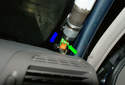 Unplug the side curtain airbag electrical connector (green arrow) by squeezing the connector and pulling it in the direction of the blue arrow.
