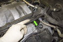 Working at the left side valve cover, pull the breather hose (green arrow) out of the mounts running under the wiring harness holder.