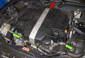 Working at the engine cover (red arrow), pull off the two front sir duct hoses (green arrows).