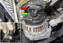 Working at the back of alternator, disconnect the electrical connector (red arrow) by pressing the release tab and pulling the connector straight off.