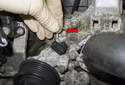Once clean, use a small flathead screwdriver and remove the coolant sensor retaining clip (red arrow).